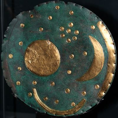 The Nebra Sky Disk. The outer gold rim on the right was also matched by one on the left, which is now missing. These marked the sunsets and sunrises of the winter and summer solstice. The moon and sun are represented in the middle, and are surrounded by stars, which are believed to represent a number of constellations, including possibly the Pleiades. (photo copyright wiki user Anagoria 17 August 2012)