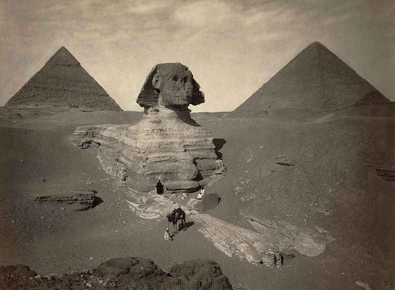 The Great Sphinx being excavated, starting in 1817 AD. Its paws are already covered in restoration stones from Roman times and a head that is obviously too small for the body, which is extremely weathered.